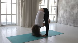 slender woman doing yoga at the window
