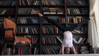 slim woman doing yoga at the closet with books at home