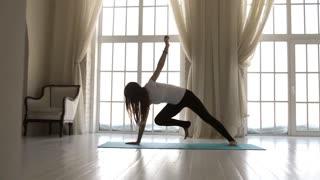 slim woman doing yoga at the window