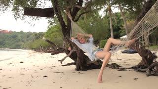 slim woman resting in a hammock on the beach