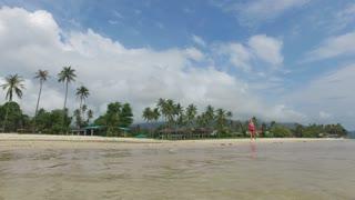 slim woman runs along the tropical beach