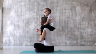 slim woman with daughter doing yoga