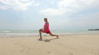 sports woman doing warm-up on the beach