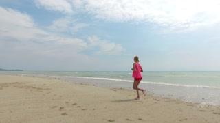 sportswoman runs along the beach