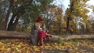 stylish mommy with daughter sit on a log in autumn park