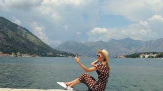 stylish woman doing selfie sitting on the lake promenade
