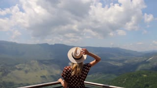 stylish woman with a hat stands overlooking the valley of the mountains