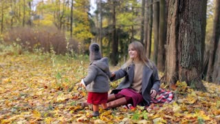 stylish woman with baby sitting in autumn park