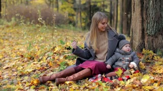 stylish woman with baby sitting in autumn parkstylish woman with baby sitting in autumn park