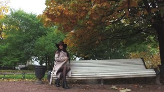 stylish young woman sits on a bench in an autumn park