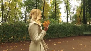 stylish young woman walking in the autumn park