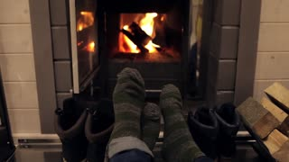 the feet of a young couple in warm socks near the fireplace