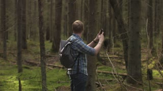 traveler takes pictures on phone in the forest