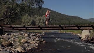 traveler with a backpack walks across a bridge across a mountain river