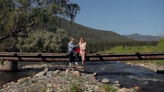 travelers with a tablet are sitting on a bridge across a mountain river
