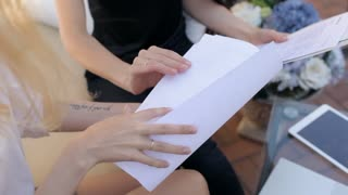 Two Business Women Discuss Working Papers, Contracts. Close-Up