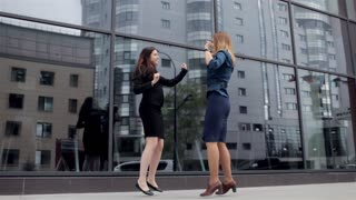 Two Business Women Rejoice and Dance Near the Business Center