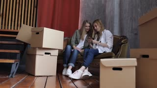 Two Girls Neighbor Are Moving, Sitting on the Couch Among the Boxes With the Phone