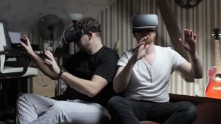 Two Men Play With Virtual Reality Glasses at Home