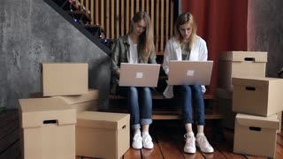 Two Women Are Moving, Sitting Among Cardboard Boxes, Using a Laptop