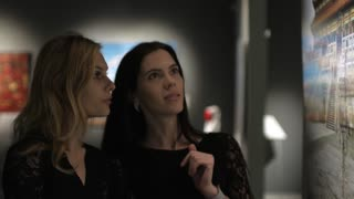 two women in a dark gallery picture