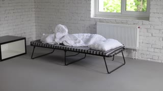 Unfolded Folding Bed in an Empty Room