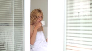 view of the open bedroom windows where a woman in a towel drinks coffee