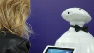 woman communicates with a modern robot