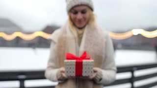 woman holding a christmas present standing by the ice rink