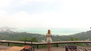 woman in a white dress is pulling her arms up, standing on a viewing platform overlooking the tropical island
