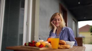 woman in pajamas eating breakfast on the balcony with fresh fruit