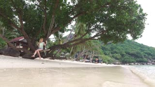 woman on a swing on the beach in the jungle