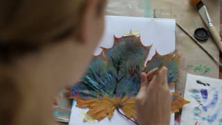 woman paints a picture on a maple leaf