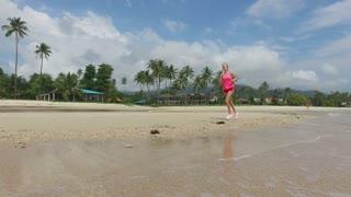 woman runs along the tropical beach