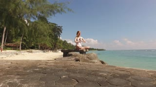 woman sitting in a yoga pose on a stony tropical beach