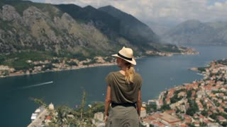 woman traveler pulls her hands up standing on a cliff overlooking the mountain bay