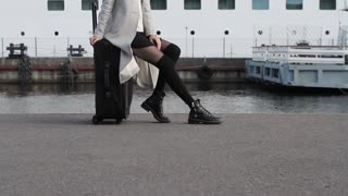 Woman Traveler Sitting on a Suitcase at Sea Cruise Liner