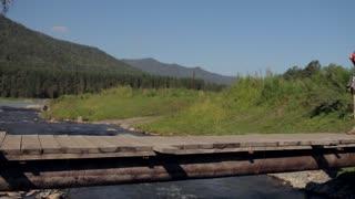woman traveler with a backpack walks across a bridge across a mountain river