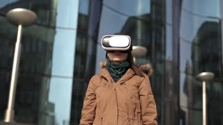 Woman Uses a Virtual Reality Glasses at a Glass Modern House
