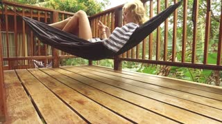 woman with a phone lies in a hammock in the tropics