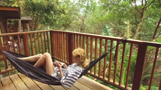 woman with a phone lies in a hammock on a balcony in the jungle
