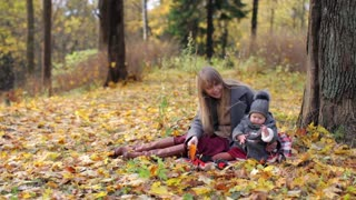 woman with baby sitting in autumn park