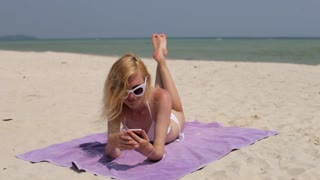 woman with phone sunbathing on the beach