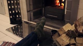 Women's feet in warm socks near the fireplace