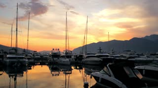 yachts and boats stand on the dock at sunset