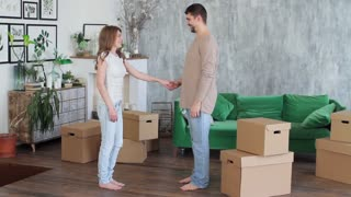 Young Couple Happy and Excited About Moving Boxes Into New Apartment