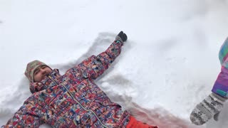 Young Couple Lying in Snow Making Snow Angels. Slow Motion