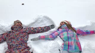Young Couple Lying in Snow Making Snow Angels
