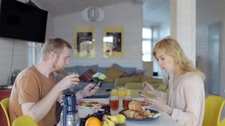 young couple with phones breakfast at table