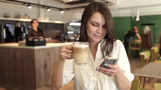 Young Girl With Phone in Cafe